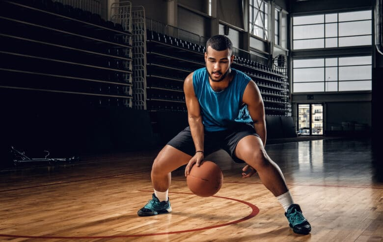 Full body portrait of Black professional basketball player in an action in basketball field.