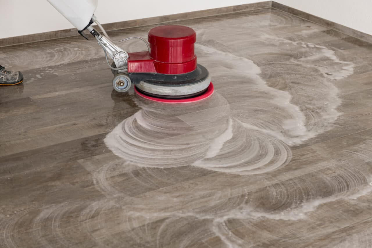 Cleaning machine drives over the tiled floor and cleans the floor.