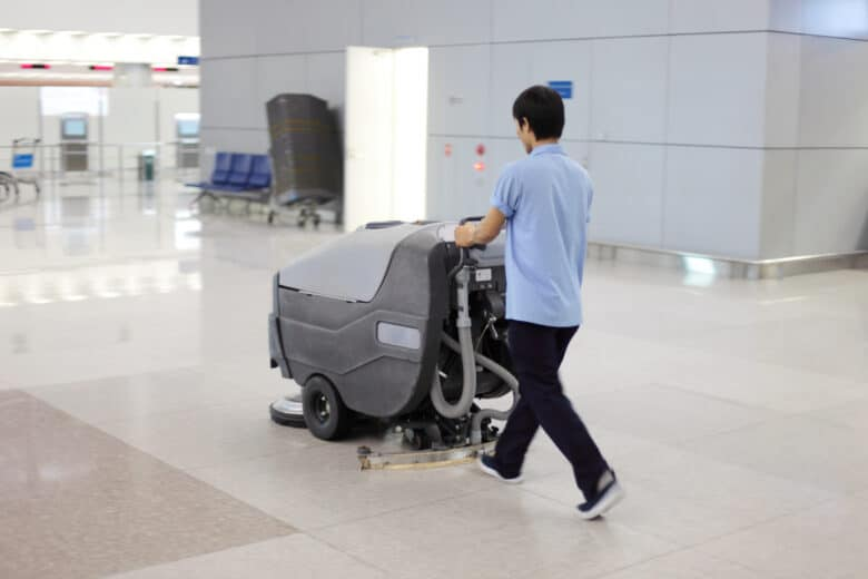 Peking, China - May 1, 2009: cleaning up; man is cleaning an airport floor (Peking) with a washer